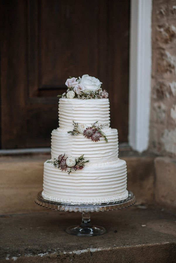 Three tier wedding cake decorated with fresh flowers