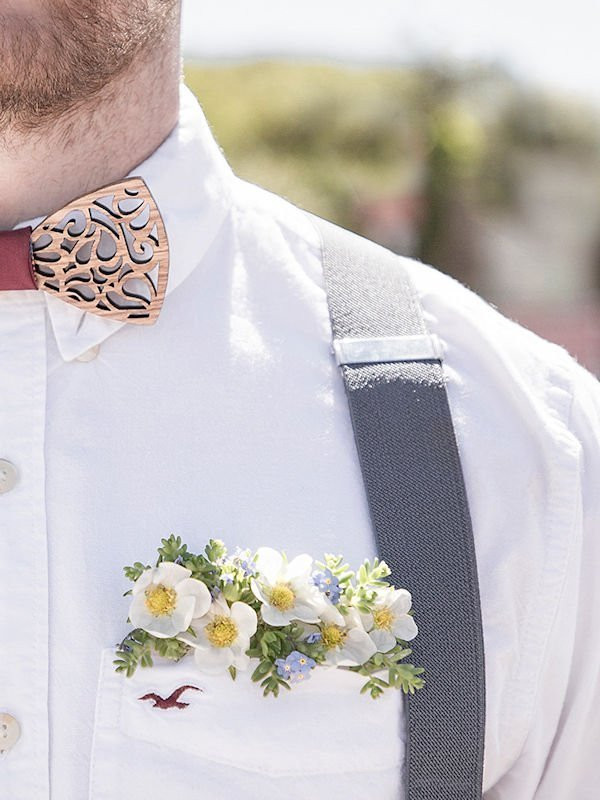 Floral pocket square modeled by groom with white shirt and blue braces