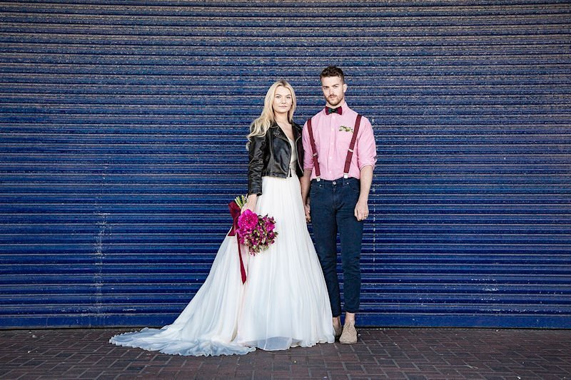 Modern bride and groom stand against a dramatic blue urban backdrop