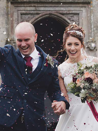 Bride and groom exiting church with confetti and bride holding an autumn bouquet